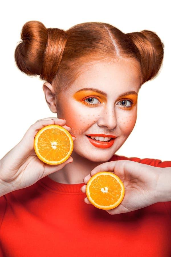Ung härlig flicka med apelsinen royaltyfria bilder