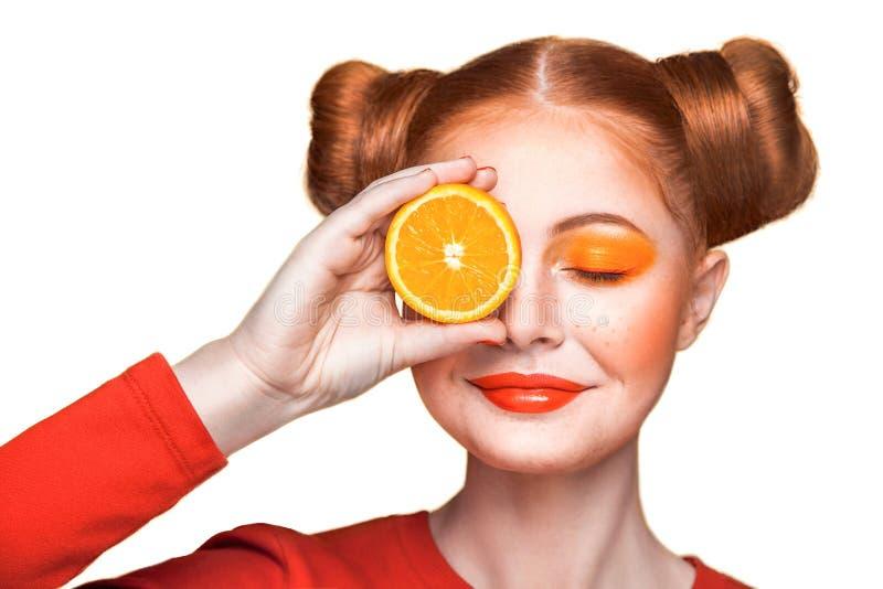 Ung härlig flicka med apelsinen arkivfoto