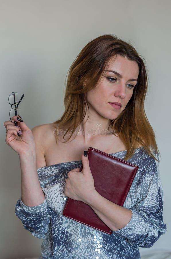 Ung härlig flicka med den långa hårläraren med exponeringsglas med en bok i hans händer efter föreläsningen arkivfoto