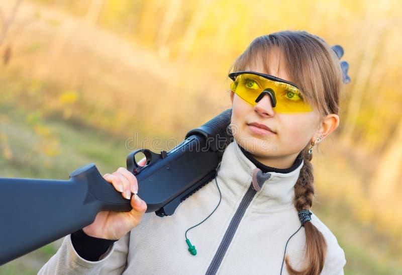 Ung härlig flicka med en hagelgevär royaltyfri bild