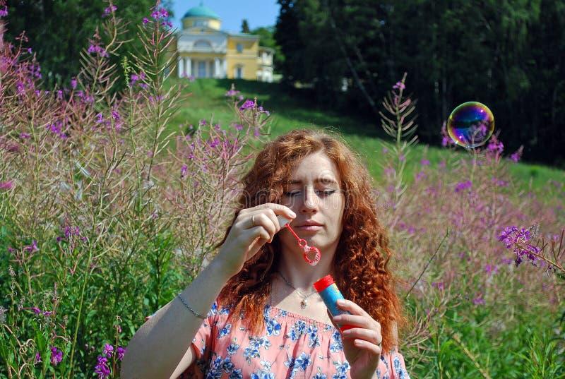 Ung härlig flicka med fräknar och lockigt rött hår som blåser bubblor royaltyfri bild