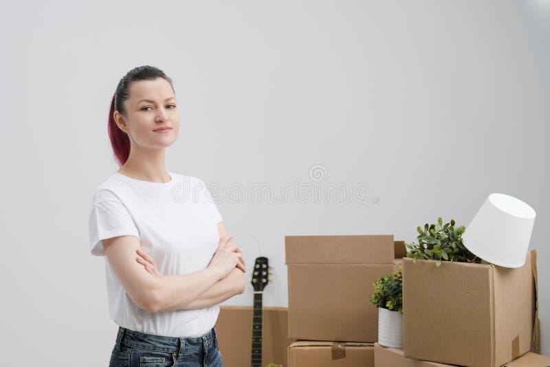 Ung härlig flicka med kulört hår i en vit T-tröja och jeans, mot bakgrunden av kartonger och fotografering för bildbyråer