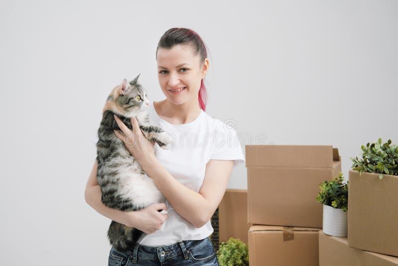 Ung härlig flicka med kulört hår i en vit T-tröja och jeans som rymmer en husdjurkatt och ut ser fönstret arkivbild