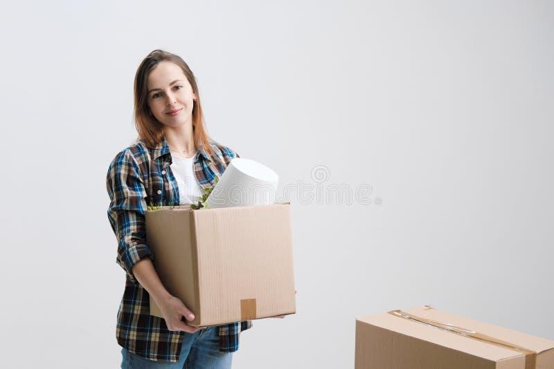 Ung härlig flicka med kulört hår i en vit T-tröja, plädskjorta och jeans, mot bakgrunden av papp arkivbild