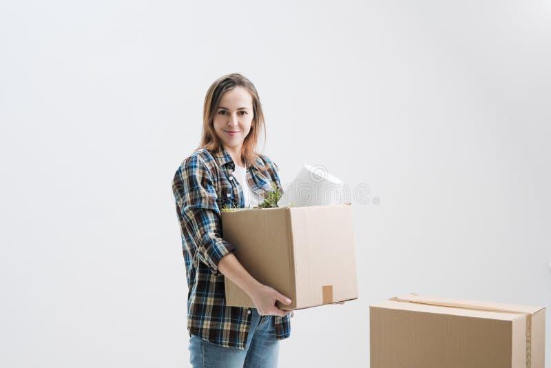 Ung härlig flicka med kulört hår i en vit T-tröja, plädskjorta och jeans, mot bakgrunden av papp arkivfoton