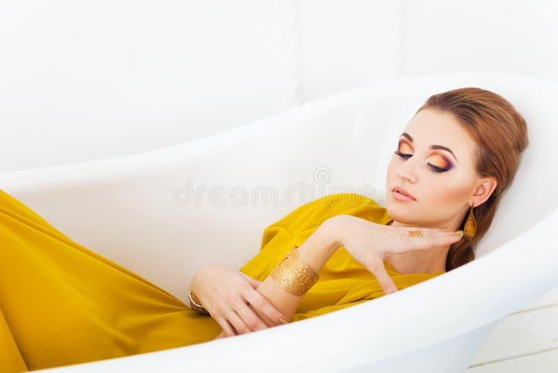 Ung härlig flicka med sminket som bär den långa gula klänningen royaltyfri foto
