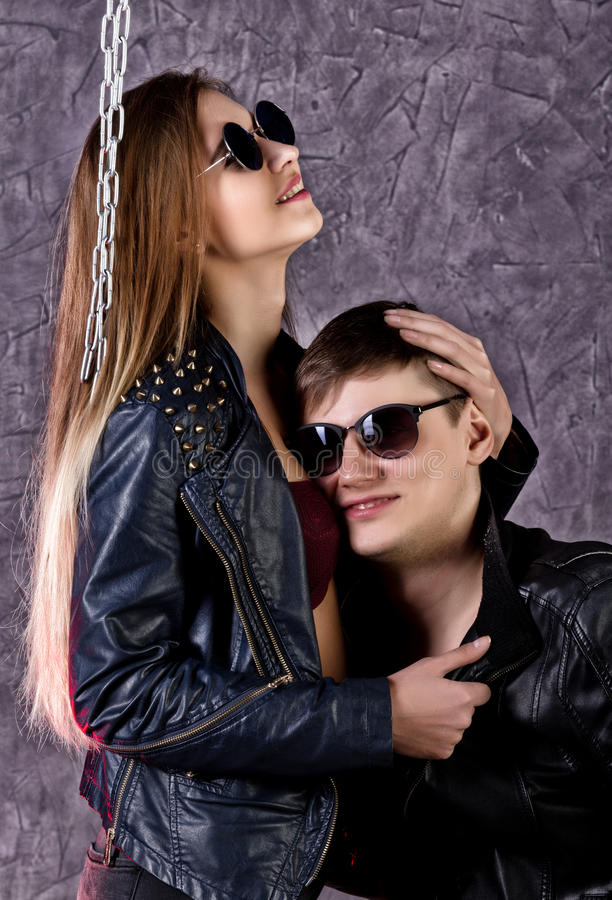 Ung härlig flicka och stilig grabb i läderomslag och solglasögon som poserar på en hög stol och kysser på grå färger royaltyfria foton