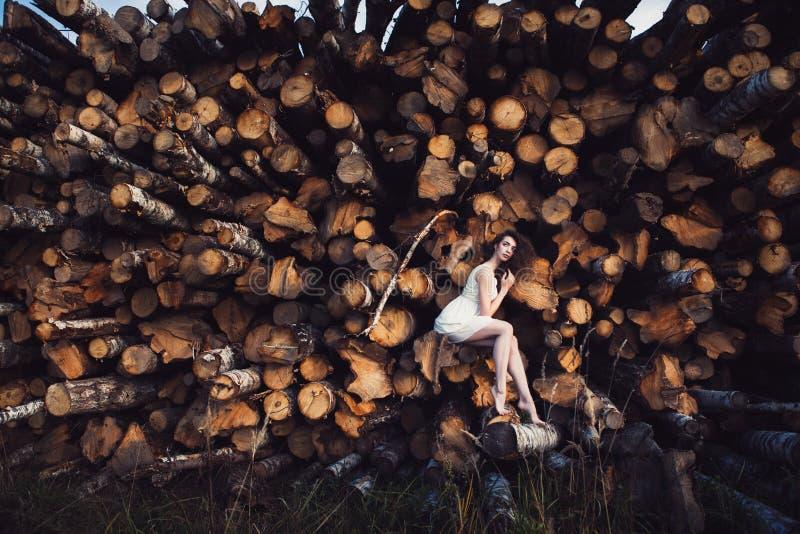 Ung härlig flicka på en bakgrund av sågade träd arkivfoton