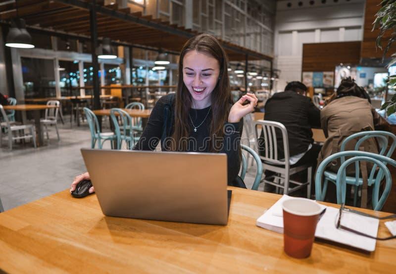 Ung härlig flicka som arbetar med bärbara datorn och dricker kaffe på en trätabell royaltyfri bild