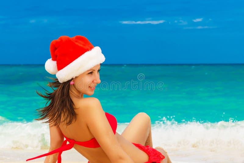 Ung härlig flicka som har gyckel i vågorna iklädda röda Sant arkivfoton