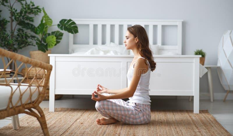 Ung härlig flicka som hemma gör yoga i lotusblommaposition royaltyfria bilder