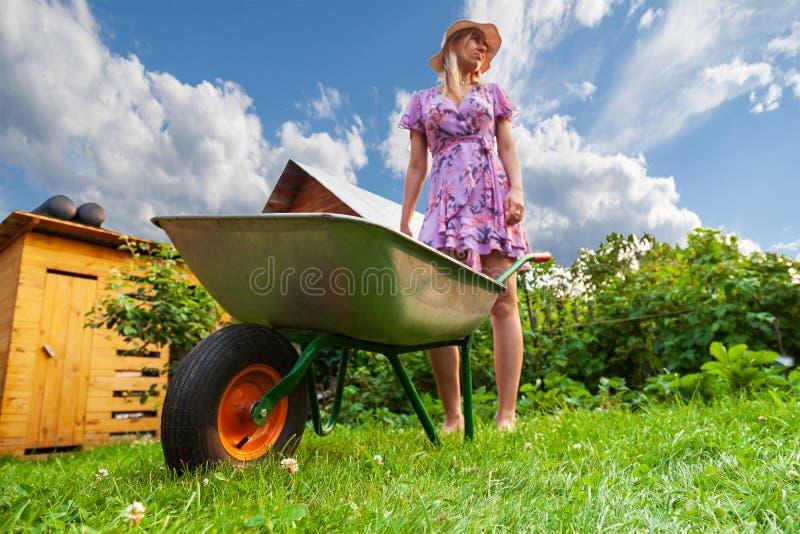 Ung härlig flickablondin i en klänning och en hatt och att ha gyckel i trädgården som rymmer i hennes händer en grön vagn och ser fotografering för bildbyråer