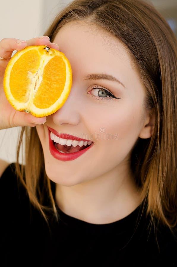 Ung härlig flickacloseupstående med orange frukt, röd läppstift och perfekt makeup arkivbilder