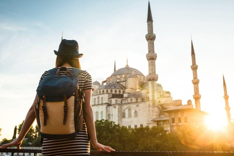 Ung härlig flickahandelsresande i en hatt med en ryggsäck som ser en blå moské - en berömd turist- dragning av royaltyfria foton