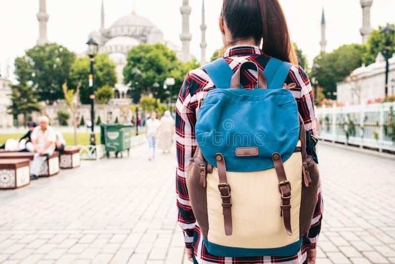 Ung härlig flickahandelsresande med en ryggsäck som ser en blå moské - en berömd turist- dragning av Istanbul Resor royaltyfri fotografi