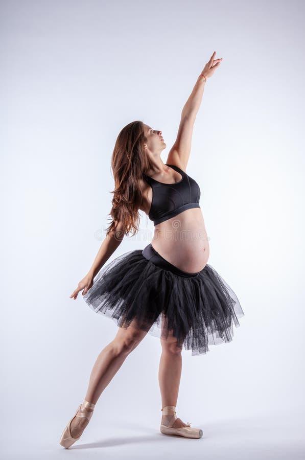 Ung härlig gravid ballerina med den svarta klänningen arkivfoto