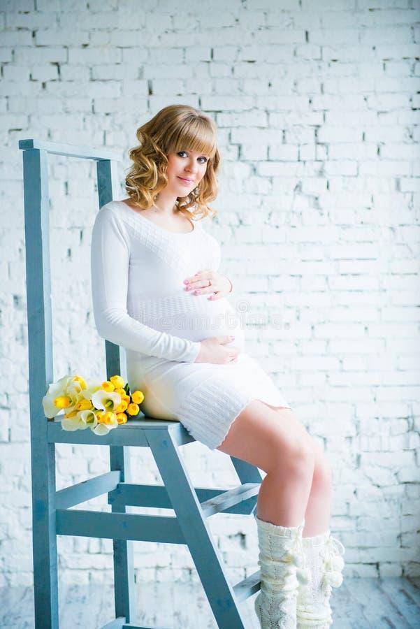 Ung härlig gravid kvinna i en vit klänning med en bukett av vita tulpan fotografering för bildbyråer