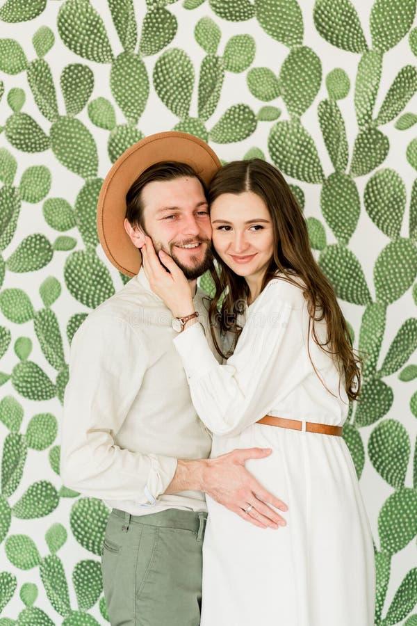 Ung härlig gravid kvinna och hennes make i hattanseende nära kaktusväggen arkivbilder