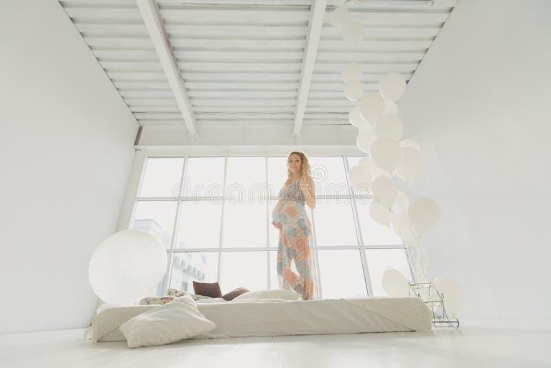 Ung härlig gravid kvinna som hemma står det near fönstret royaltyfria foton