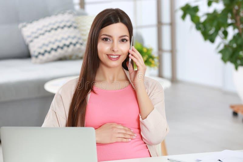 Ung härlig gravid kvinna som talar vid telefonen, medan arbeta royaltyfria foton