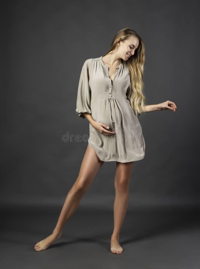 Ung härlig gravid långbent blond kvinna som bär en kort ligh arkivfoto