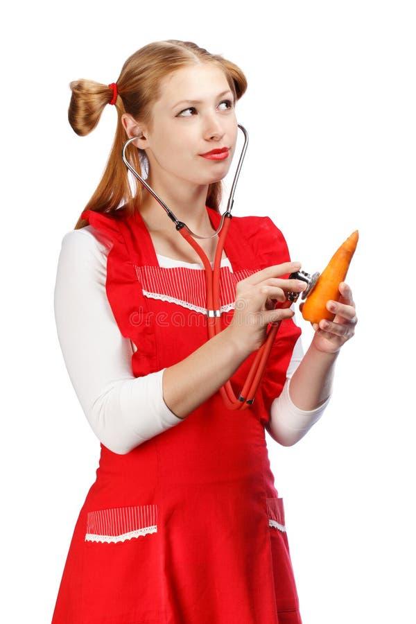Ung härlig hemmafru i ljust rött förkläde med rolig ponytai arkivfoton