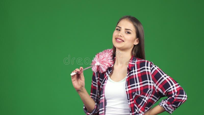 Ung härlig hemmafru som ler rymma en dammtrasa på chromakeybakgrund arkivfoton