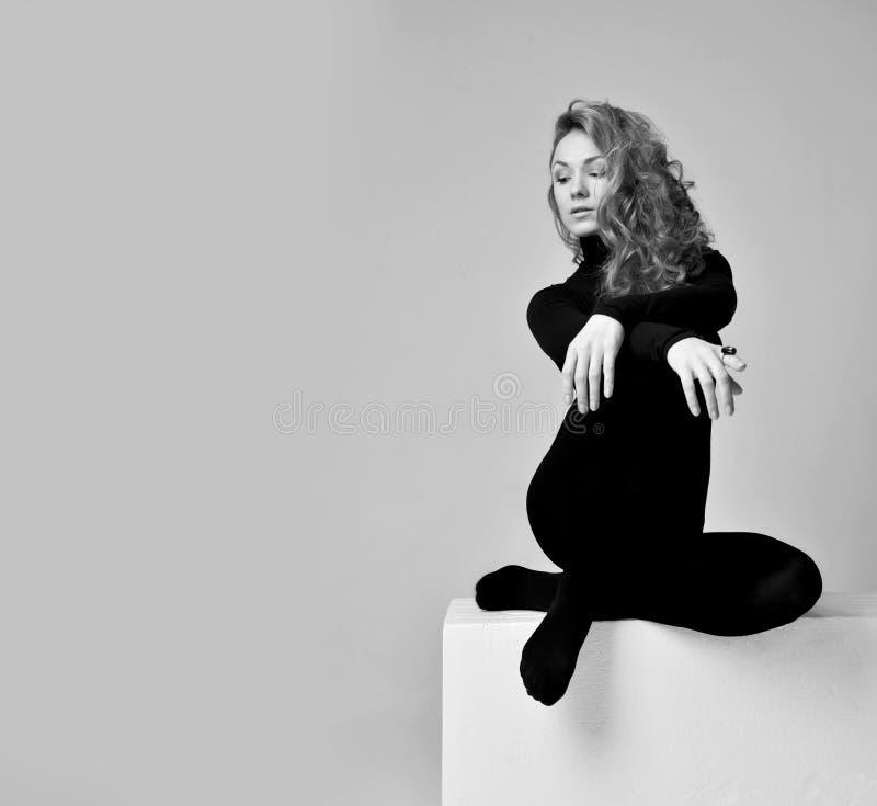 Ung härlig hipsterflickakvinna som poserar i långt torkdukesammanträde för mörk kropp på henne knä som ser kameran royaltyfri bild