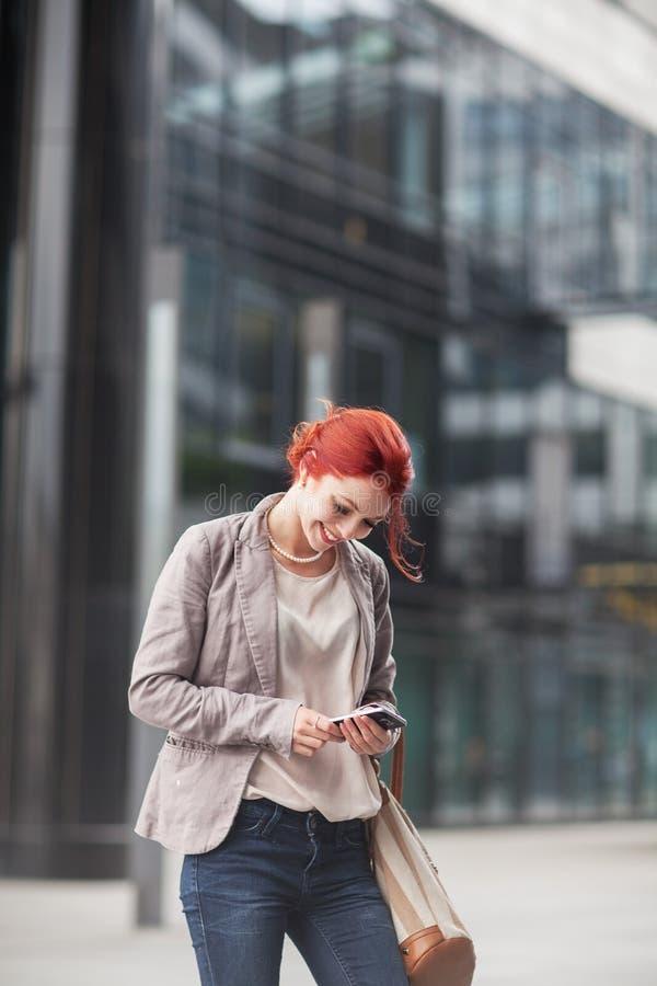 Ung härlig holdingmobile telefon för affärskvinna som arbetar i centrum, utomhus royaltyfri fotografi