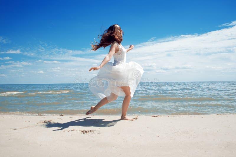Ung härlig hoppa brunettkvinna i den vita klänningen arkivbilder