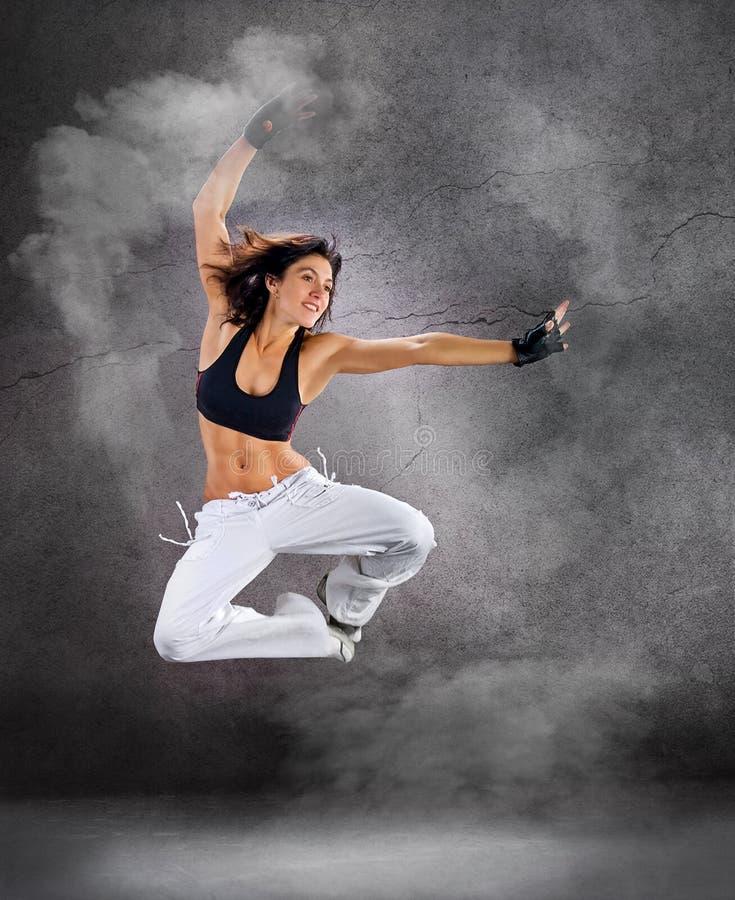 Ung härlig idrotts- kvinnabanhoppning som dansar modern stildanshöft-flygtur på studio på väggbakgrund med rök royaltyfri foto