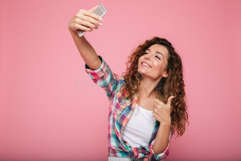 Ung härlig isolerad kvinnadanandeselfie på övre gest för smartphone och för visningtumme royaltyfri fotografi