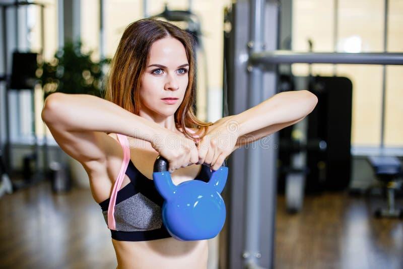 Ung härlig konditionkvinna som utarbetar med hantlar i idrottshall arkivfoton