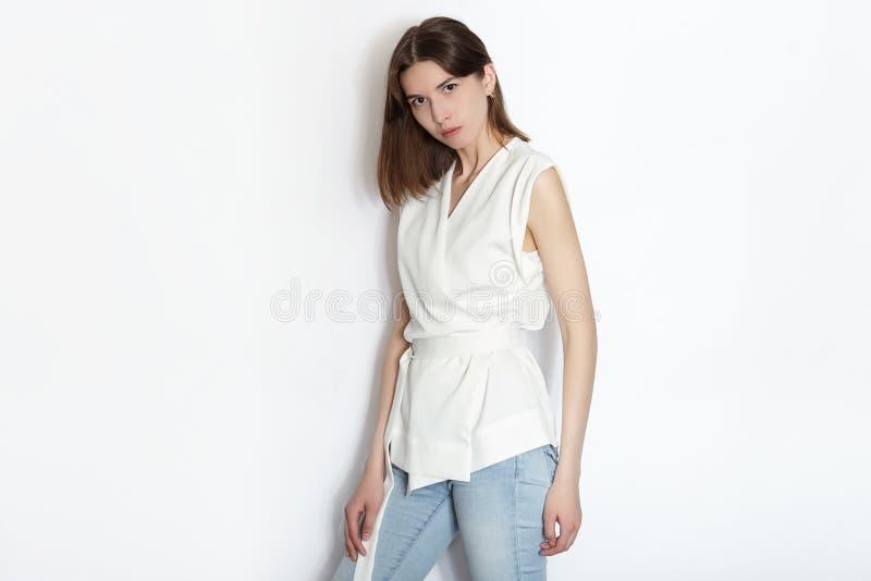 Ung härlig kvinna för brunettnybörjaremodell som öva posera visningsinnesrörelser på vit väggstudiobakgrund fotografering för bildbyråer