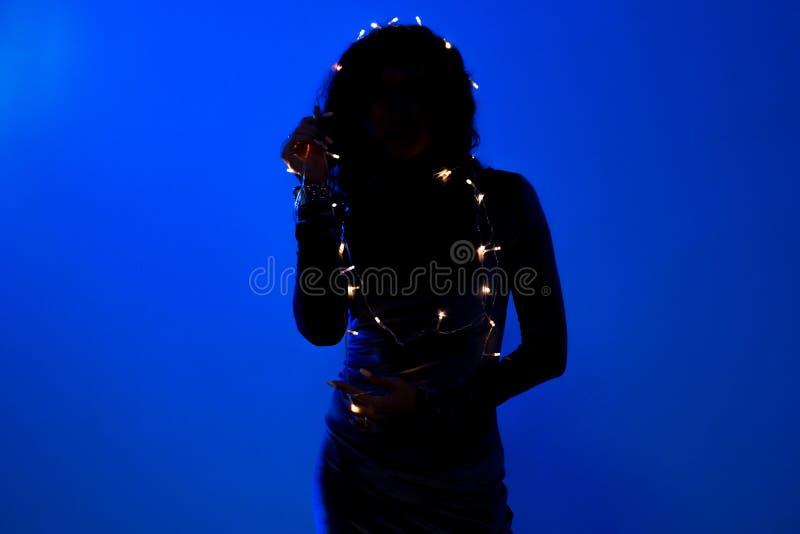 Ung härlig kvinna för svart kontur på mörkt - blå bakgrund royaltyfri fotografi