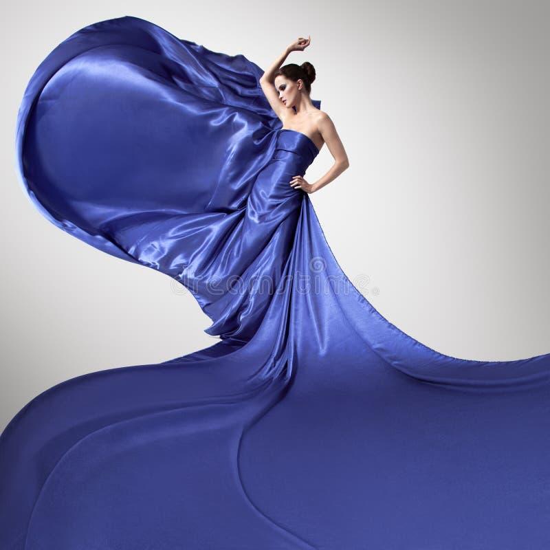 Ung härlig kvinna, i att fladdra blåttklänningen arkivfoton