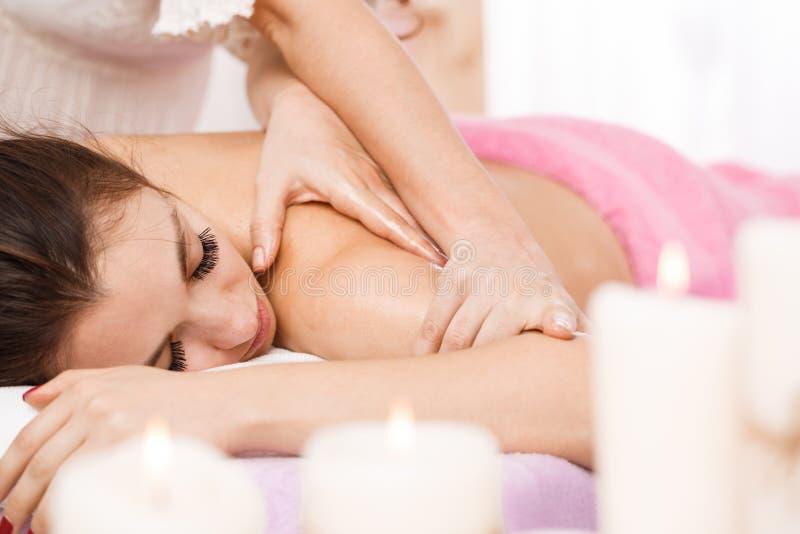Ung härlig kvinna i brunnsortsalongen som har avslappnande massage för kropp arkivbild