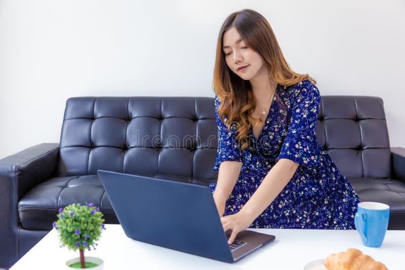 Ung härlig kvinna i den blåa klänningen som arbetar på hennes dator i hennes hem- vardagsrum royaltyfri foto
