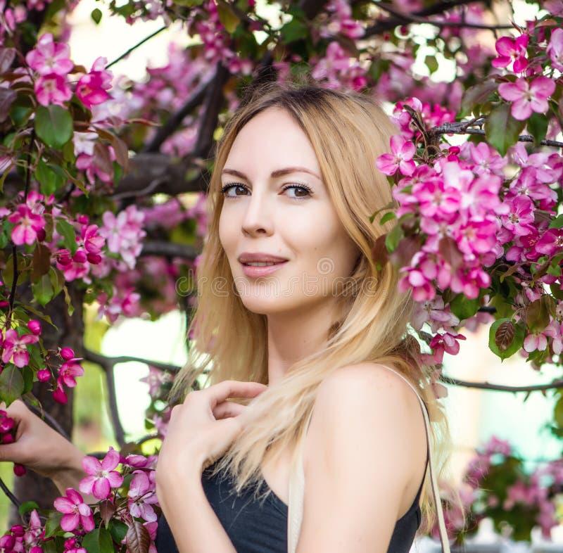 Ung härlig kvinna i den Japan sakura trädgården arkivbilder