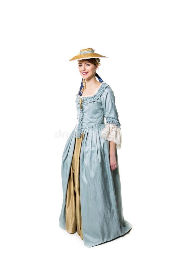 Ung härlig kvinna i den långa medeltida klänningen som isoleras på vit arkivfoton