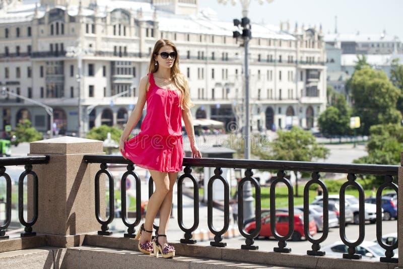 Ung härlig kvinna i den röda korta klänningen som utomhus poserar i sunn royaltyfria foton