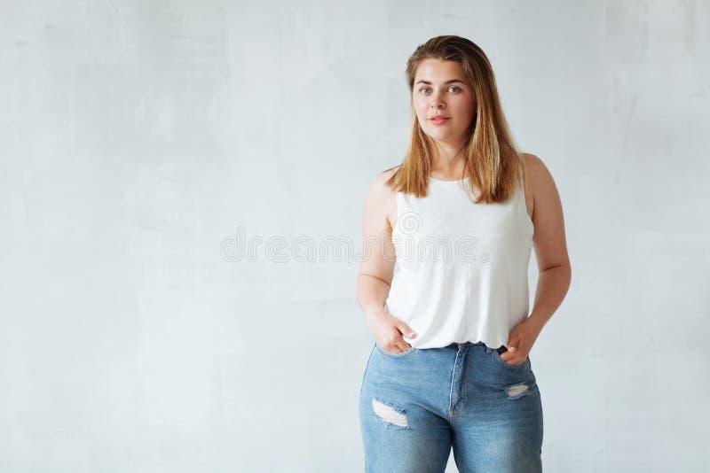 Ung härlig kvinna i den vit skjortan och jeans royaltyfria foton