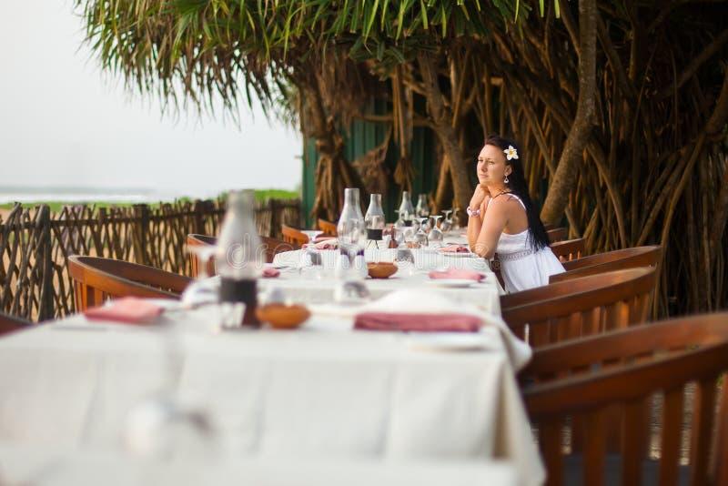 Ung härlig kvinna i den vita klänningen på kusten av det tropiska havet i ett kafé Lopp- och sommarbegrepp arkivbild