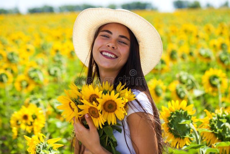 Ung härlig kvinna i en sugrörhatt och med en bukett av blommor i ett fält av solrosor arkivfoton