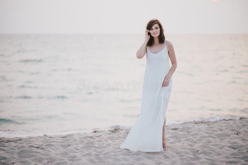 Ung härlig kvinna i en vit klänning som går på en tom strand nära havet arkivbilder