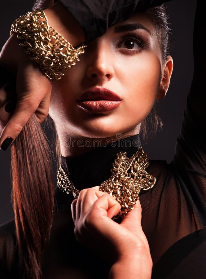 Ung härlig kvinna i ett halsband och ett armband arkivfoto