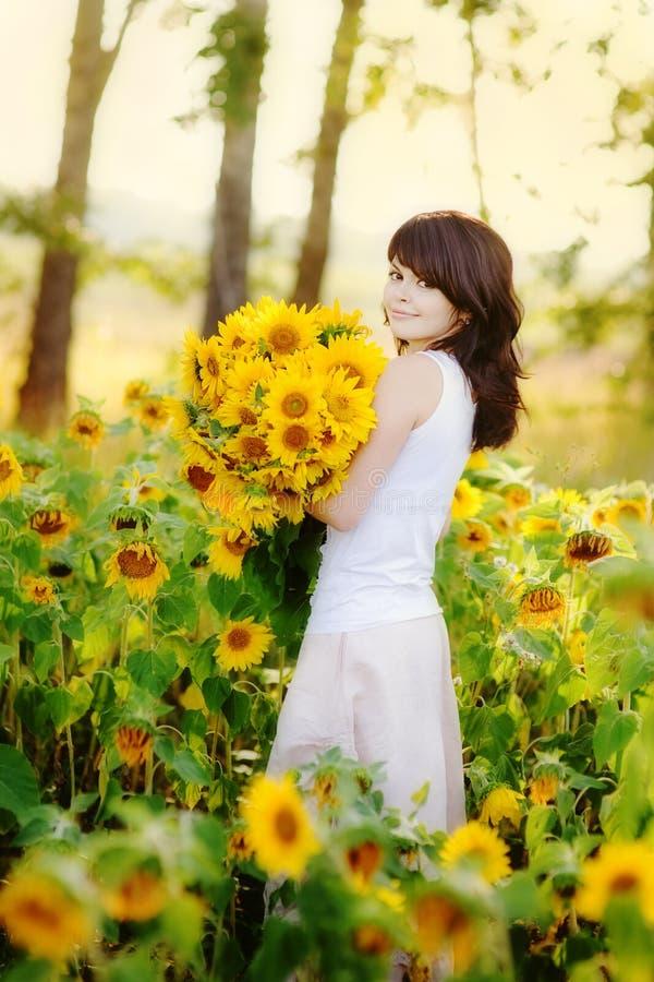 Ung härlig kvinna i ett solrosfält arkivbild