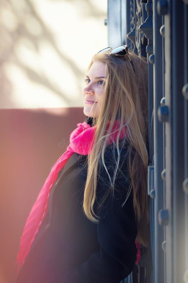 Ung härlig kvinna i ett svart lag och en rosa halsduk royaltyfri foto