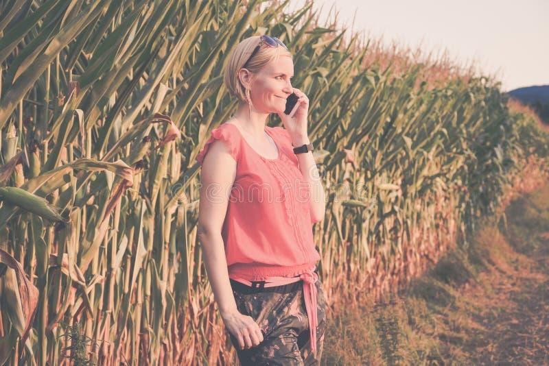 Ung härlig kvinna i färgrikt utomhus- samtal för torkdukar och för solglasögon på mobiltelefonen royaltyfria foton