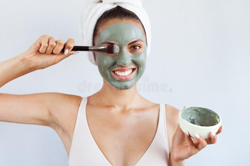 Ung härlig kvinna i framsidamaskering av terapeutisk blå gyttja Spa royaltyfri fotografi